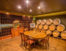 Oak Barrel Room featuring a table, a wall full of wine and barrels stacked high