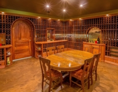 Oak Barrel Room showing table and two walls full of wine bottles